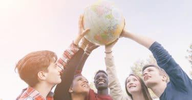 Grupo de jovens segurando o globo do mundo para cima.