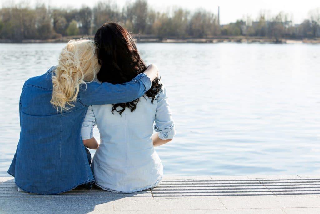 Duas mulheres sentadas na beira de um lago observando a paisagem, sendo uma mulher loira e uma morena.