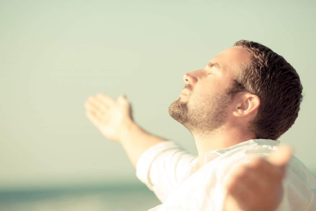 Homem branco, jovem, na praia, com os braços aberto olhando para cima.