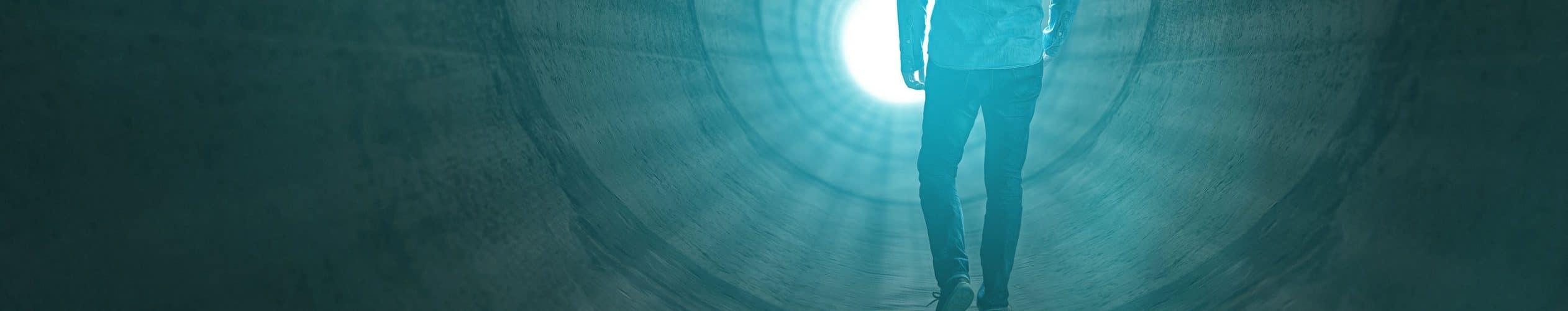 Homem caminhando para a luz no fim do túnel