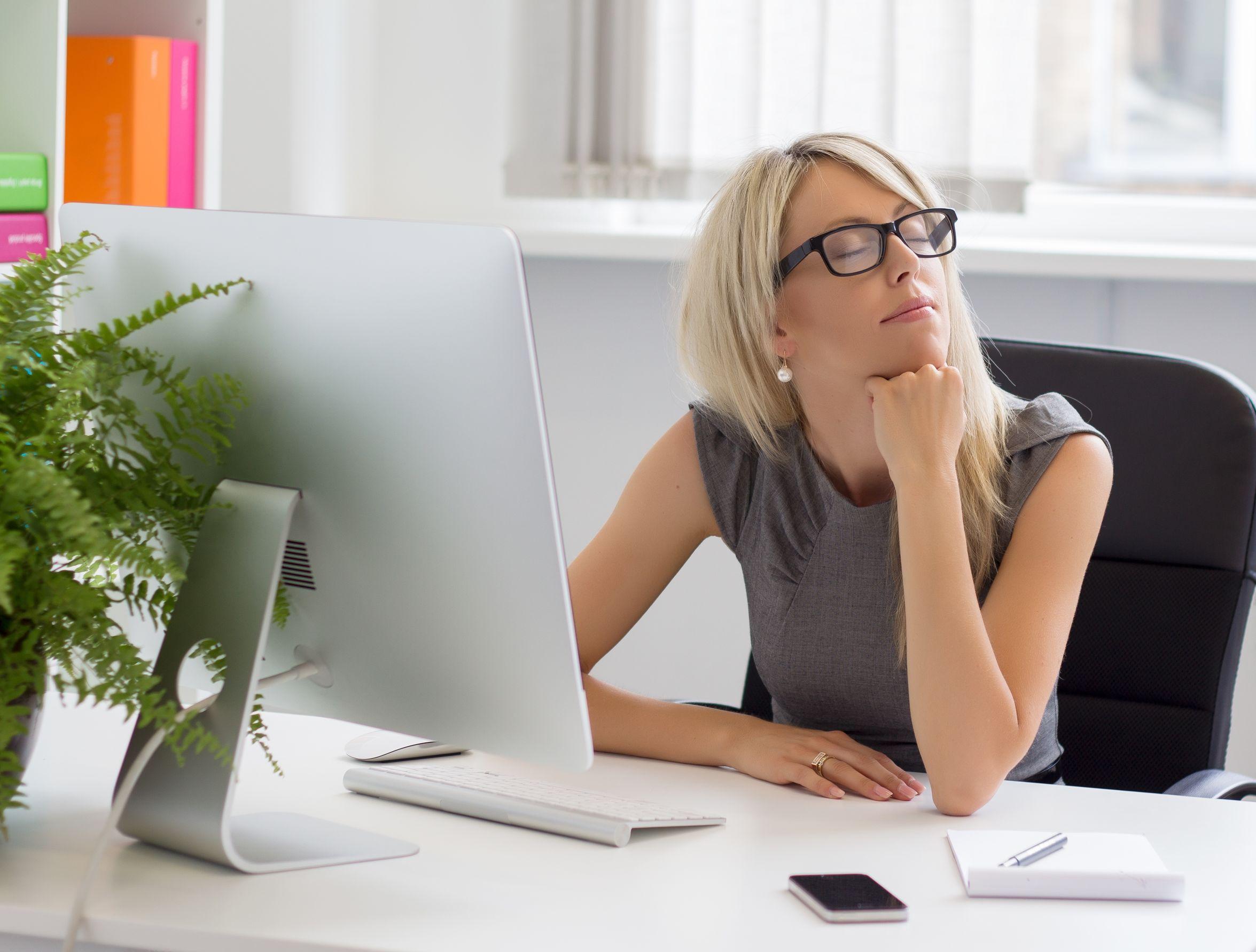 Mulher pensando em sua vida profissional, se terá sucesso. Loira e usa óculos.
