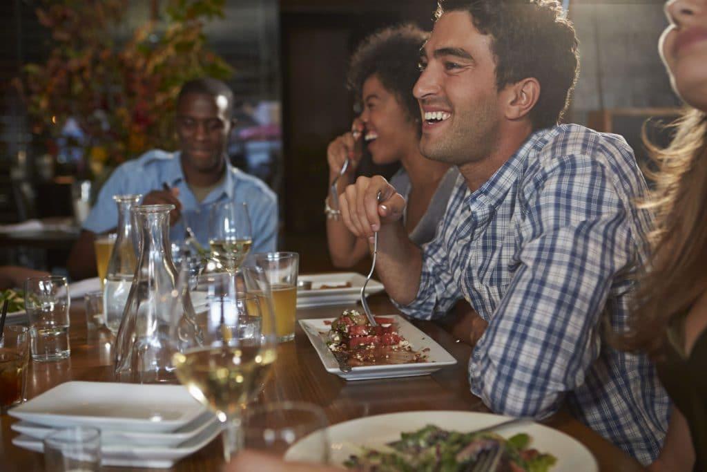 Amigos de diversas etnias, sentado ao redor de uma mesa de restaurante, todos comendo e rindo.