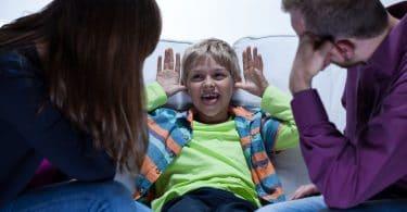 Criança com Transtorno do Déficit de Atenção com Hiperatividade sentada no sofá, fazendo caretas para os seus pais.