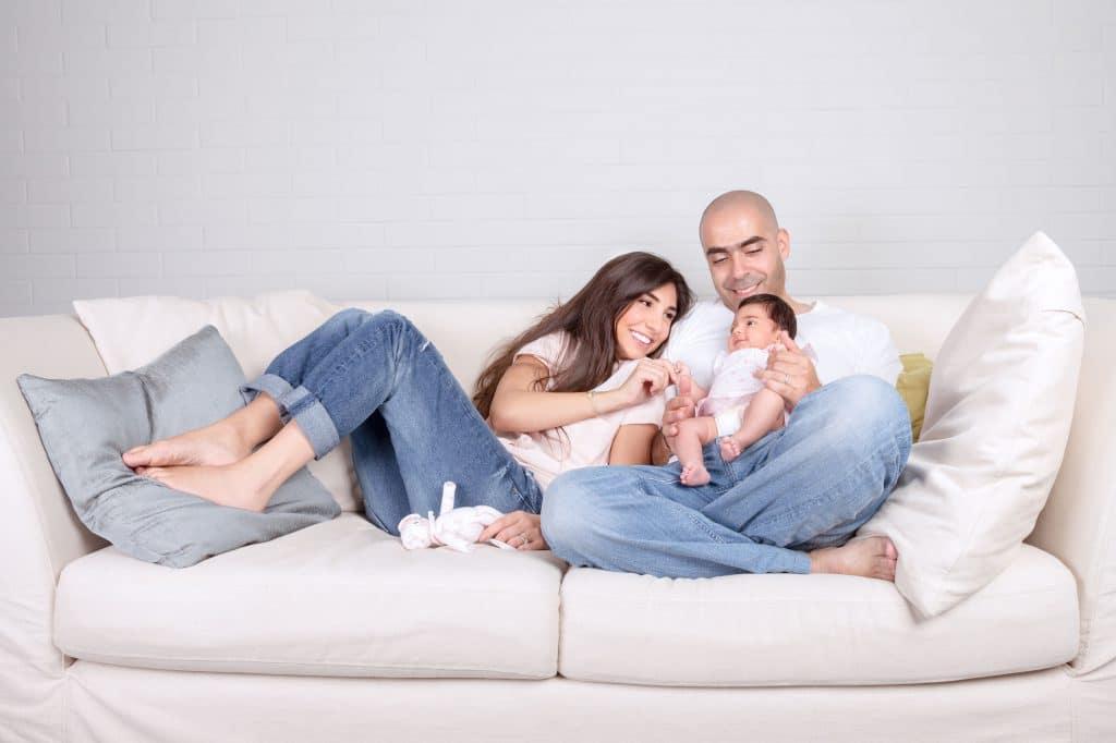 Homem e mulher brancos, sentados em um sofá branco, no meio de uma sala branca, ondem o homem segura um bebê.