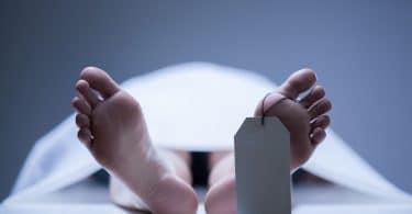 Foto próxima de pés de um corpo humano colocado em uma mesa de necrotério.