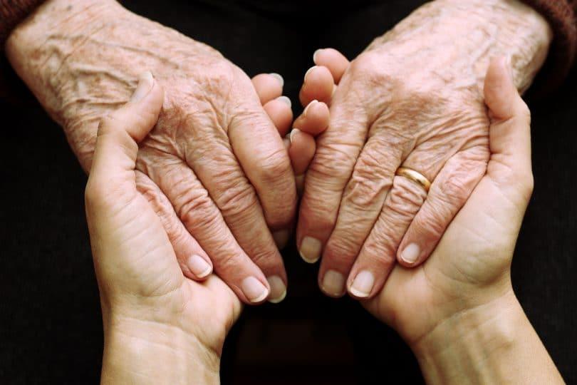 Mãos de um idoso ou idosa e mãos de uma jovem. Gerações se encontrando.