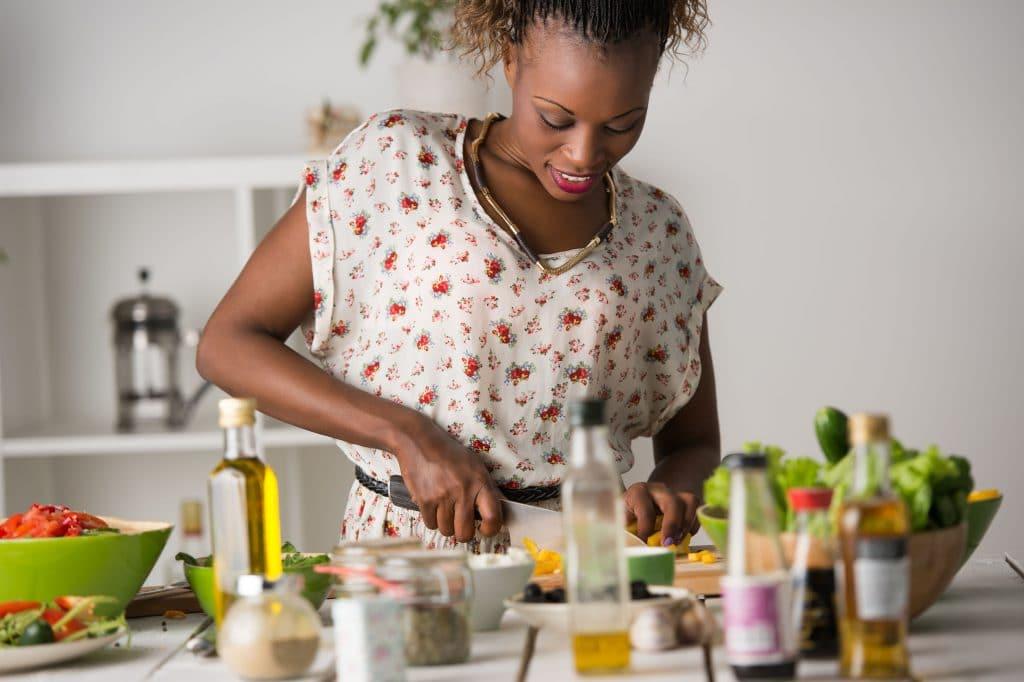 Mulher negra jovem e sorridente em uma cozinha branca cortando vegetais para fazer uma salada, cercada de utensílios e outras comidas e temperos.