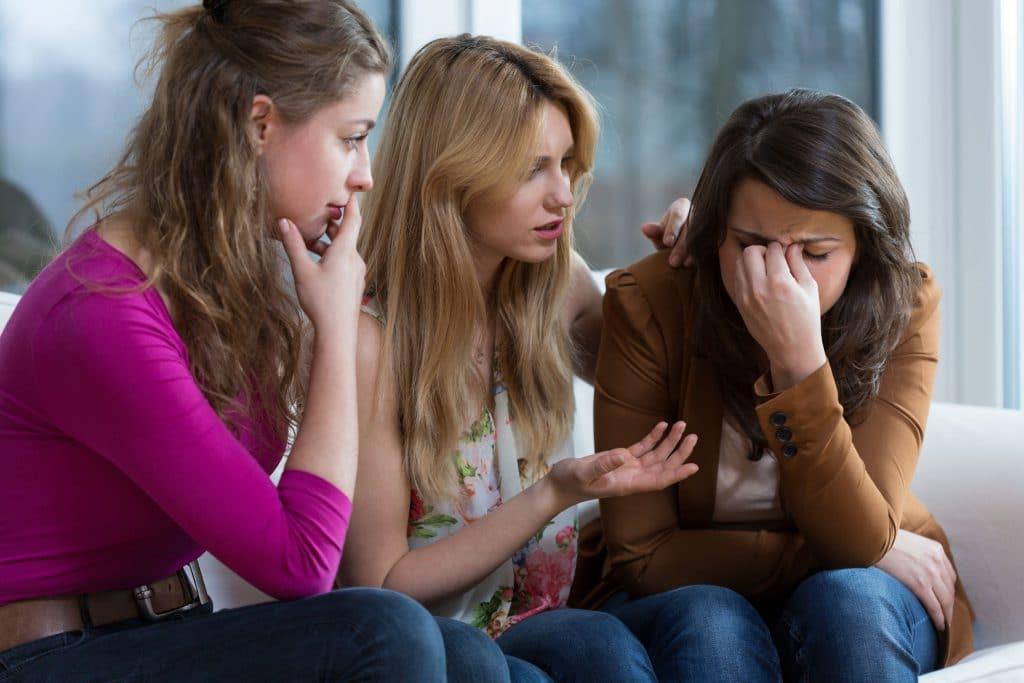 Três mulheres sentadas em um sofá, com uma delas chorando e as outras duas tentando consolá-la.