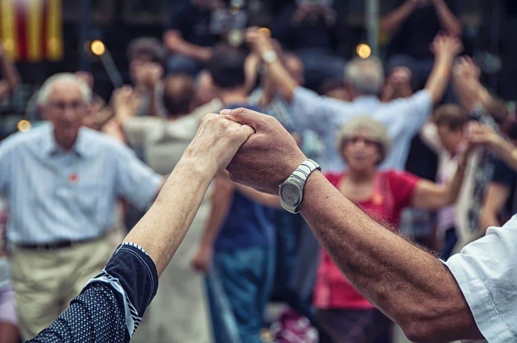 Grupo de idosos segurando as mãos em rodas. Celebrando suas culturas.