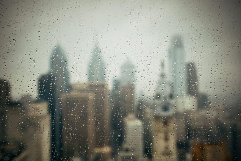 Vista de uma cidade de uma janela com o vidro molhado.