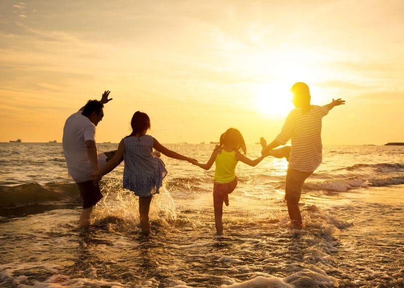 Família composta por homem, mulher e duas crianças, correndo no mar, com pôr do sol ao fundo.