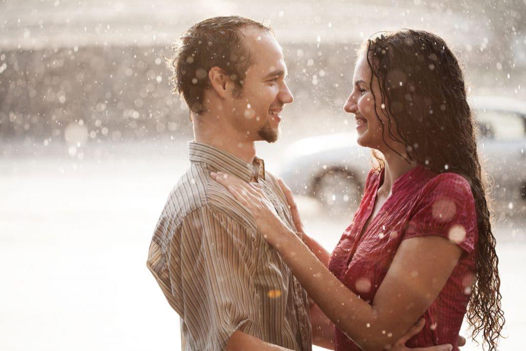 Casal tomando chuva juntos de frente um para o outro.
