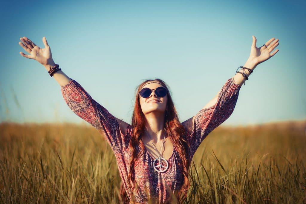 Mulher hippie com os braços abertos para o céu.