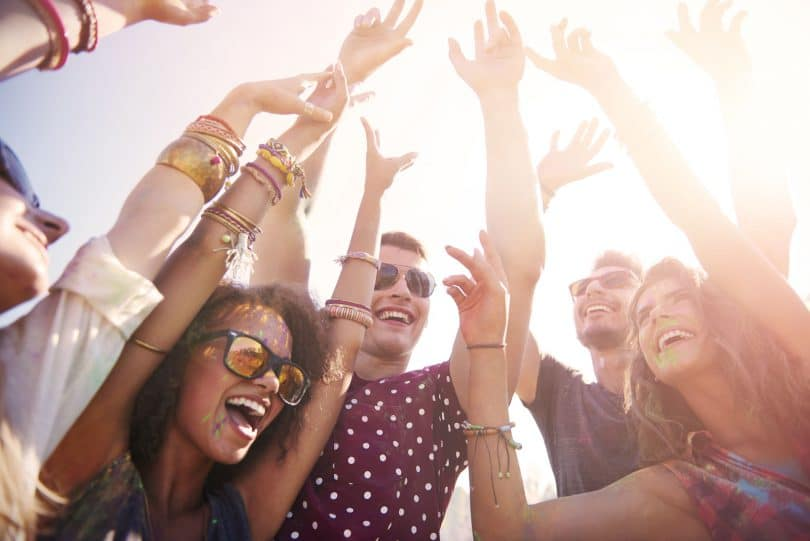 Festa à luz do dia. Grupo de amigos dançando com as mãos para cima.