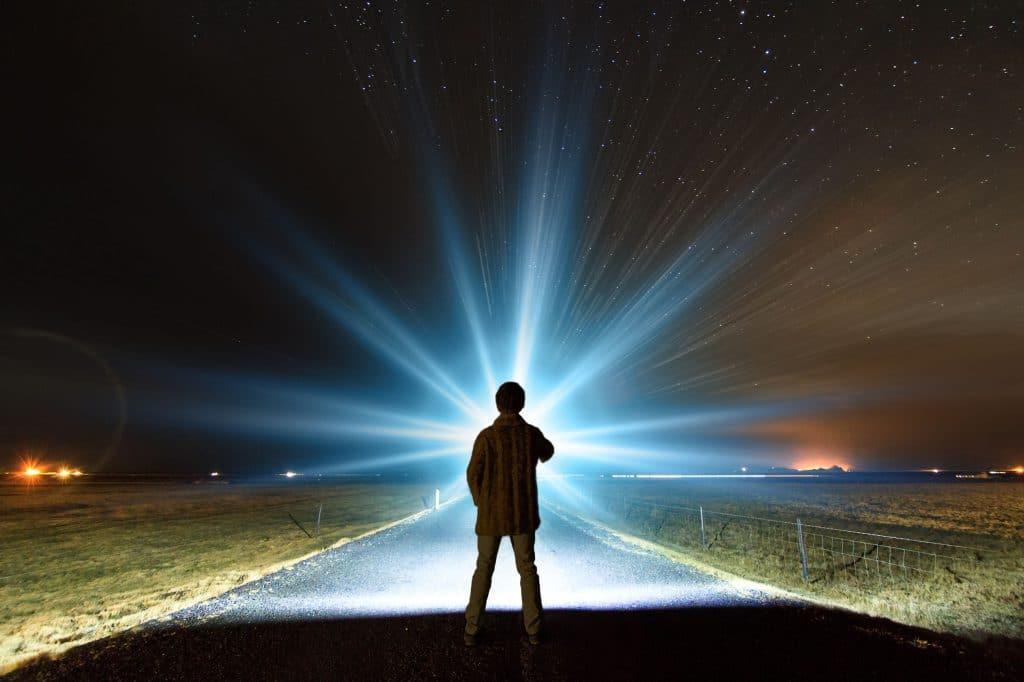 Silhueta de homem paro em uma estrada rural, olhando em direção à uma luz brilhante no horizonte noturno.