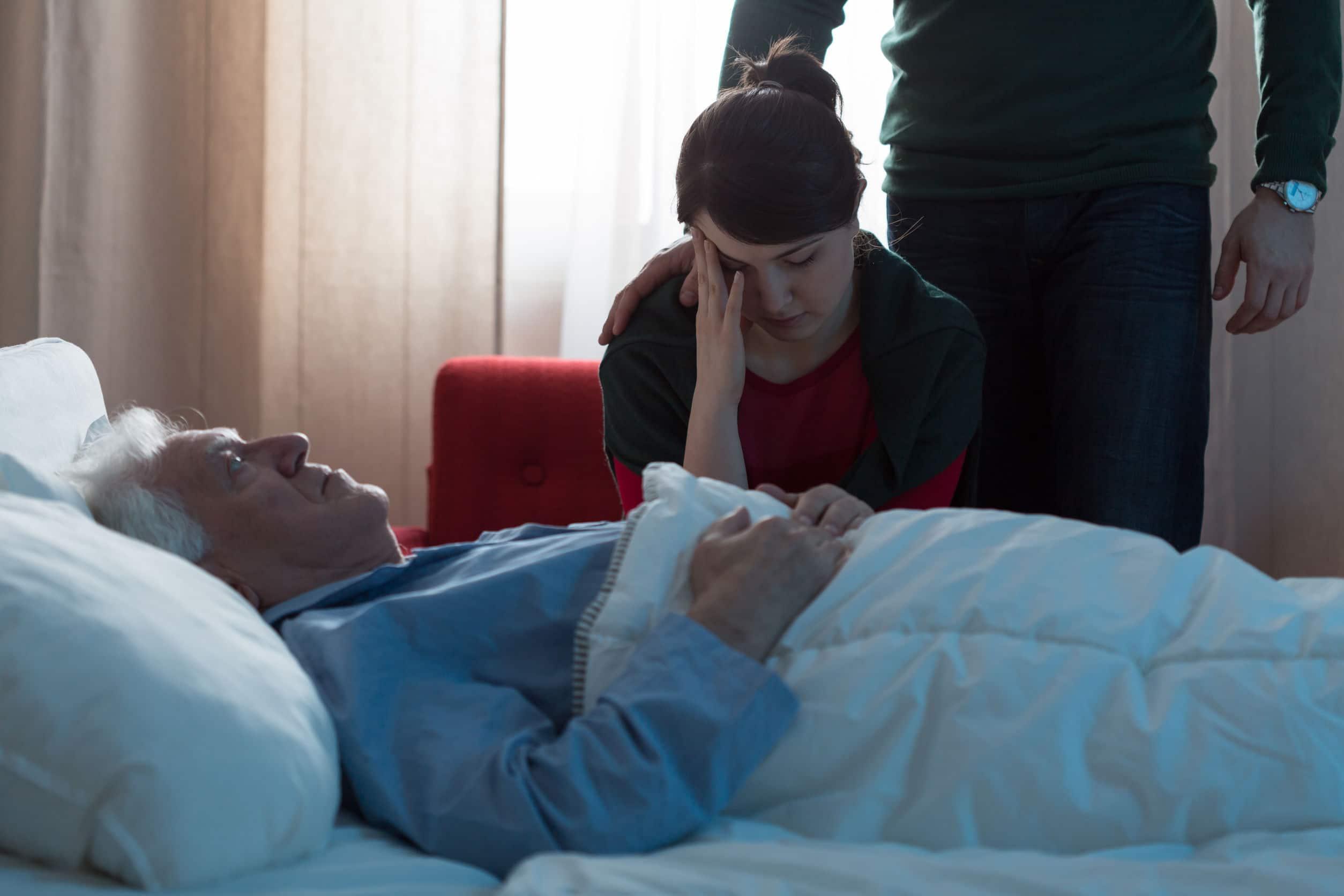 Mulher cabisbaixa triste sentada ao lado de uma cama com senhor de idade deitado.