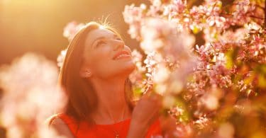 Mulher jovem e sorridente observando as flores em um jardim num dia ensolarado.