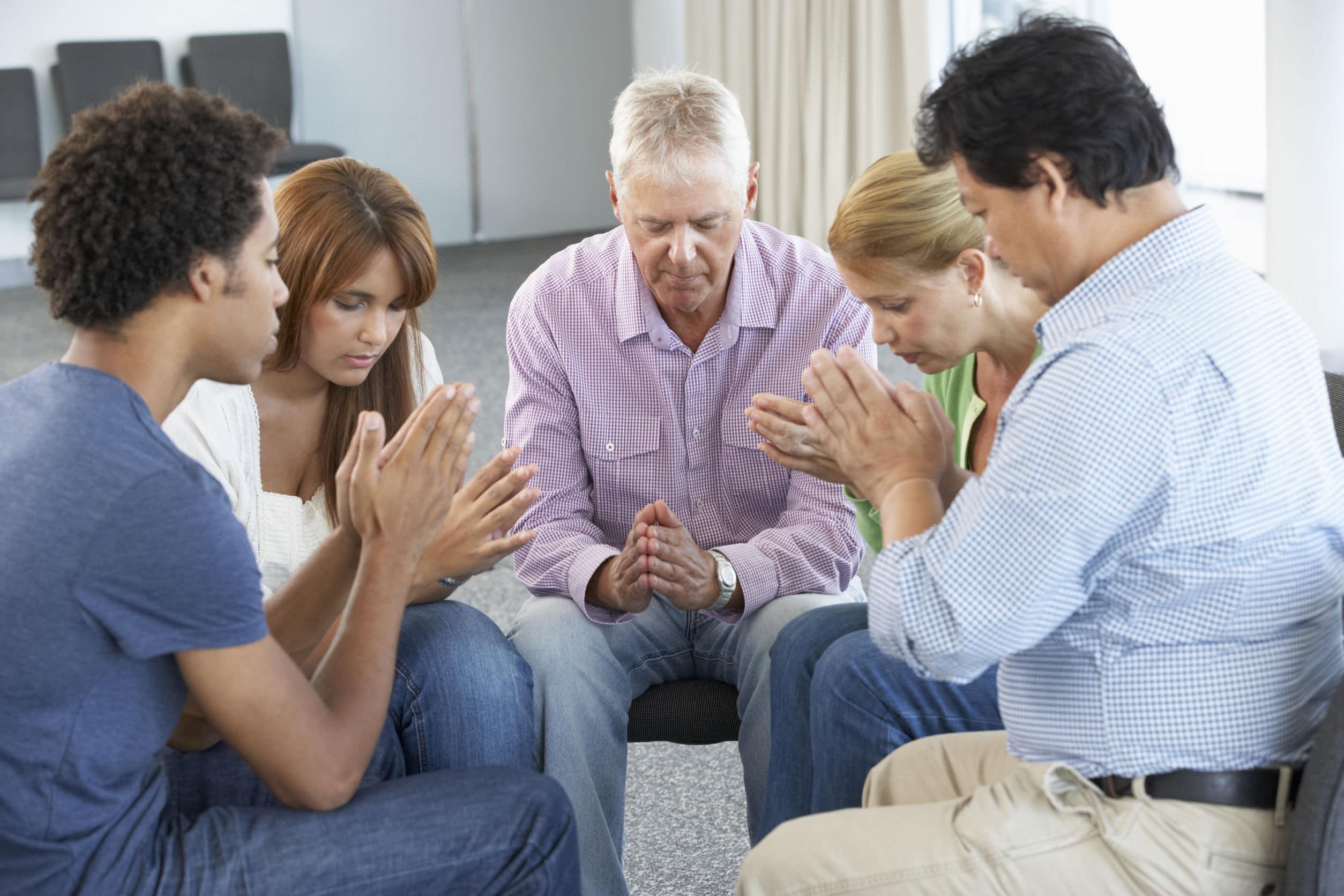 Grupo de pessoas de diversas etnias sentados formando um círculo, todos orando com as mãos juntas.