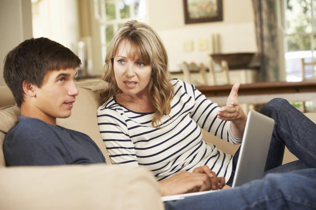 mãe e filho sentados em um sofá da sala. O menino está mexendo em um notebook e ignorando sua mãe, que está brigando com ele.