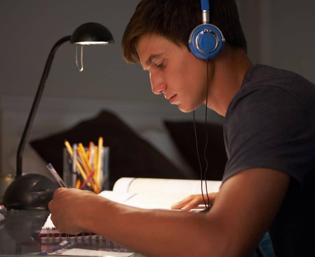 Menino branco usando fones de ouvi azuis escrevendo em um caderno com um livro aberto do lado, como se estivesse estudando.