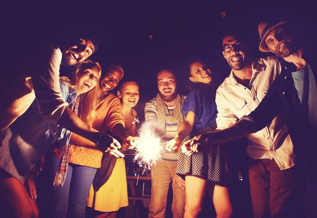 Grupo de pessoas de diferentes etnias, todas sorridentes, a noite, segurando velas com faíscas acesas.