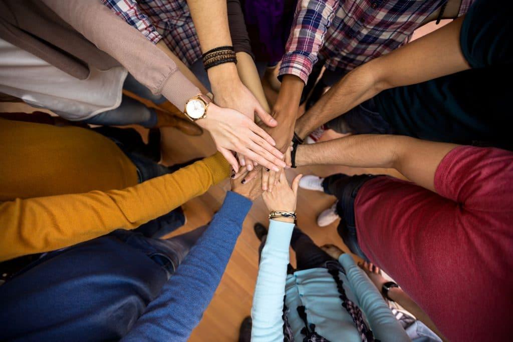 Pessoas comemorando a diversidade colocando as mãos no meio de um circulo.