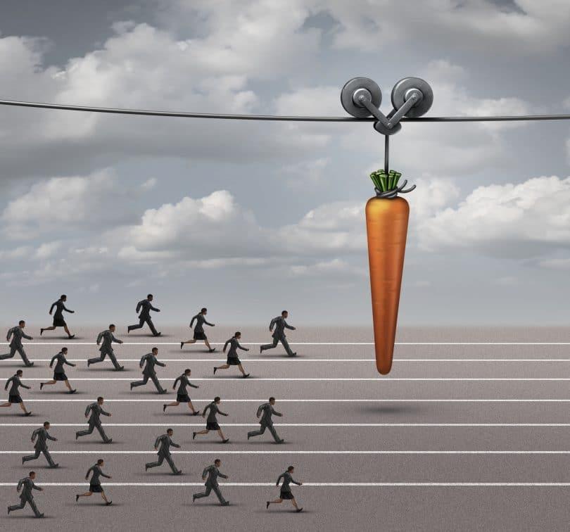 Diversas pessoas vestidas de roupas sociais correndo em pista de corrida, perseguindo uma cenoura gigante .