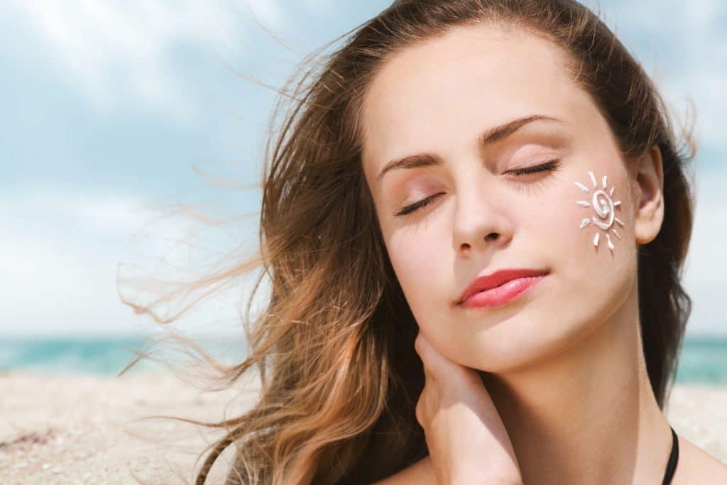 Mulher branca com filtro solar no rosto em uma praia.