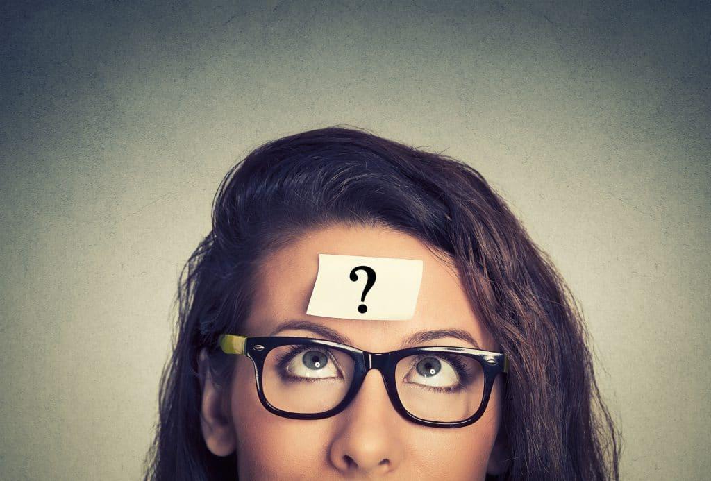mulher pensando com um ponto de interrogação no fundo da parede cinza