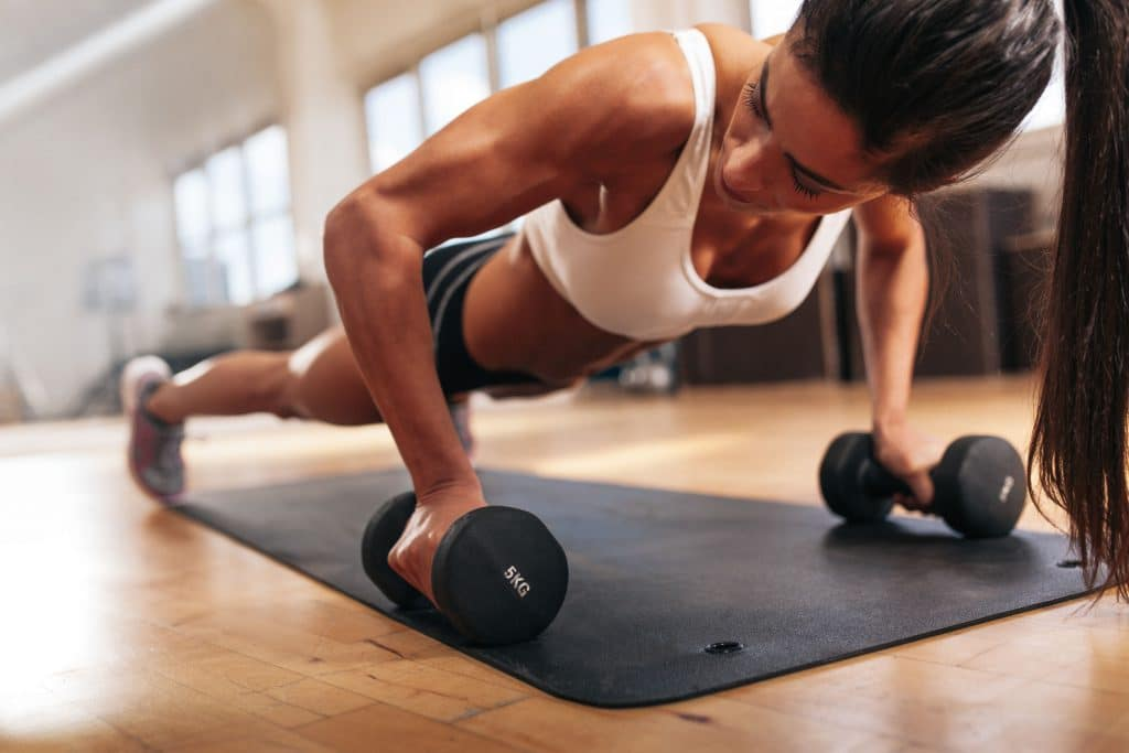 Mulher na academia fazendo treino de musculação.