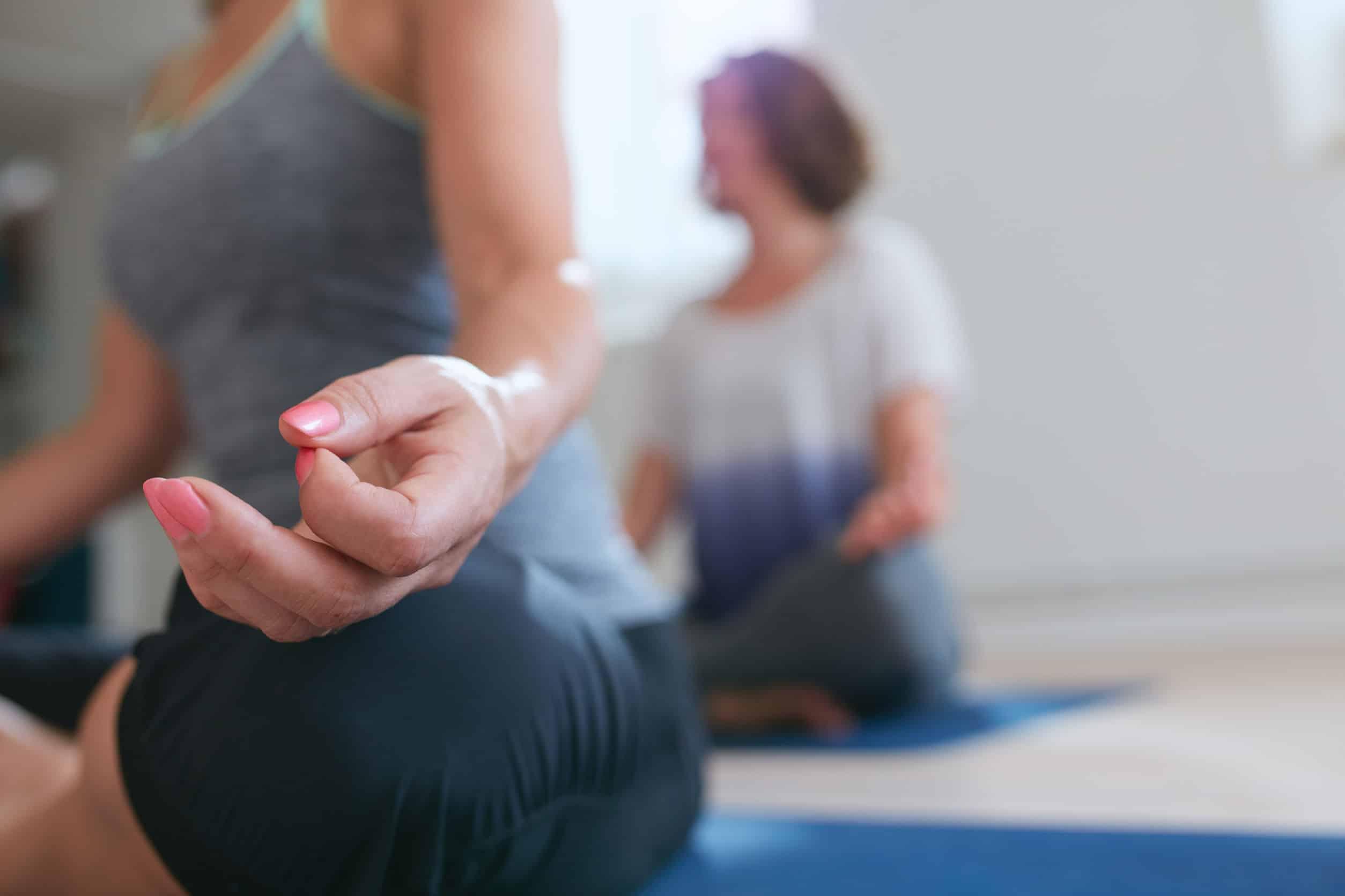Mulher sentada meditando em aula de Yoga.
