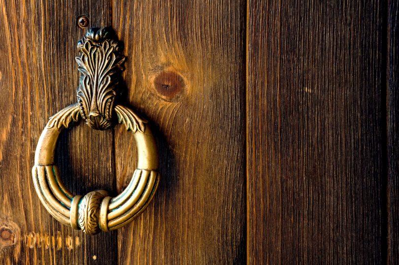 Batedor de porta em metal velho. Porta de madeira.