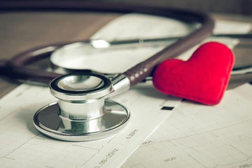 estetoscópio em cima de uma mesa com coração de pano e eletrocardiograma