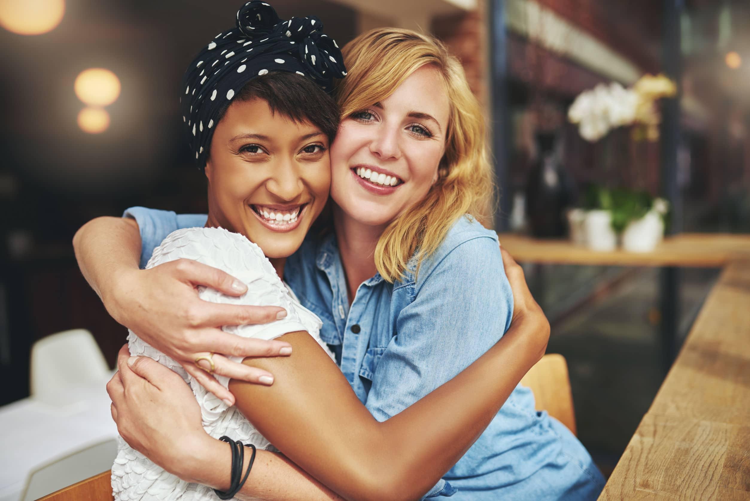 Mulher negra e mulher branca sorridentes se abraçando enquanto estão sentada na mesa de um restaurante.