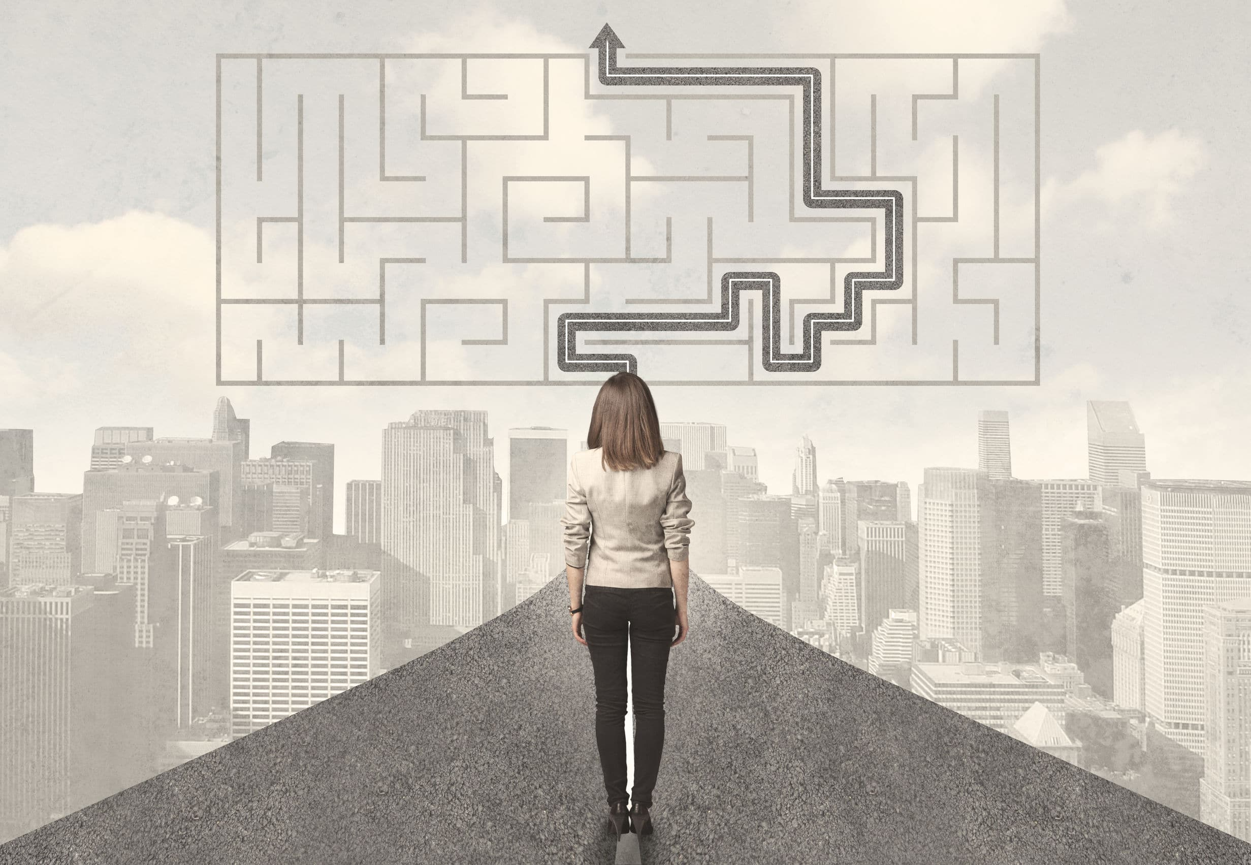 """Mulher parada em frente de uma estrada, observando paisagem de cidade, com uma imagem de """"jogo de labirinto"""" resolvido desenhada no céu."""