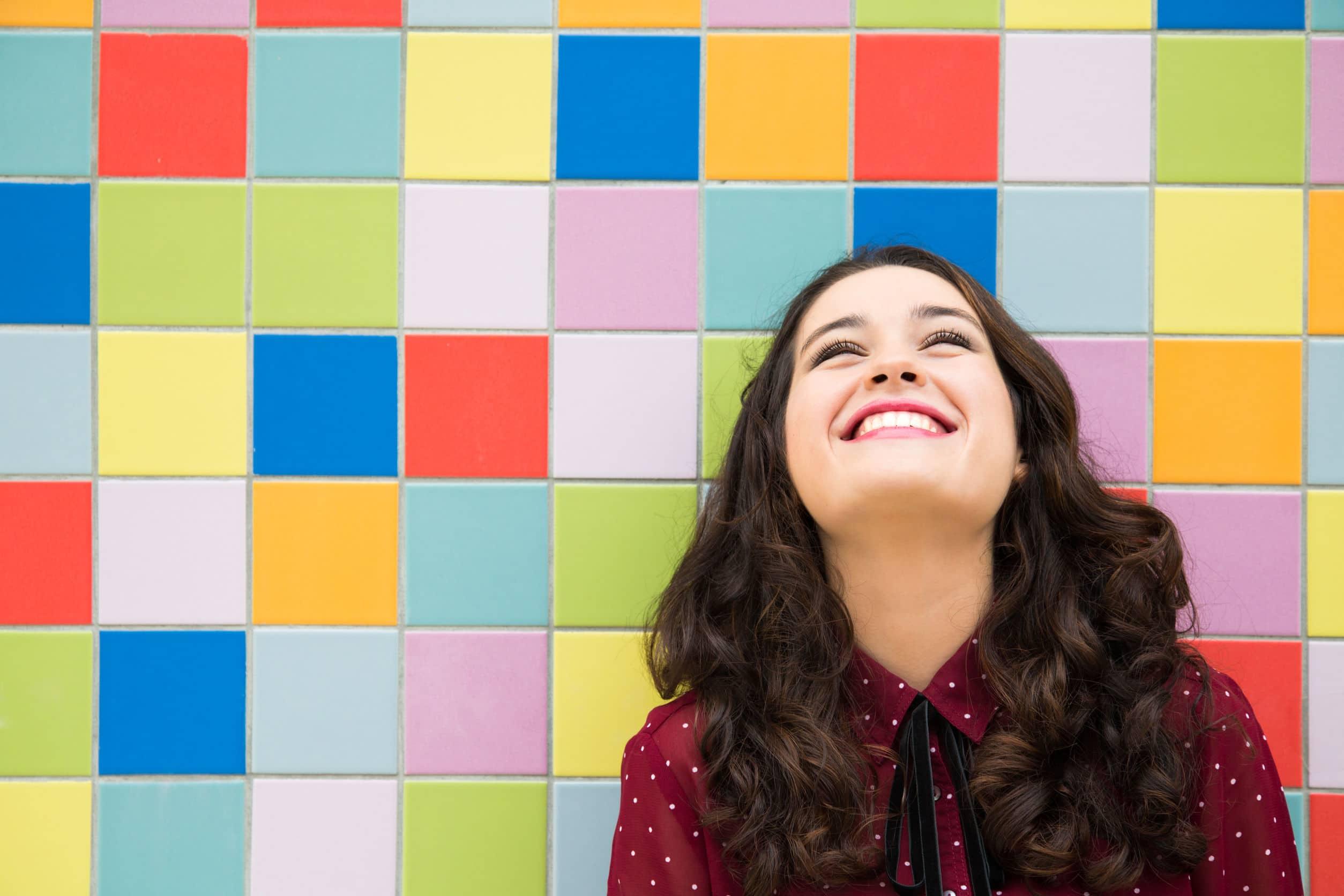 Menina feliz sorridente encostada em uma parede com azulejos coloridos.