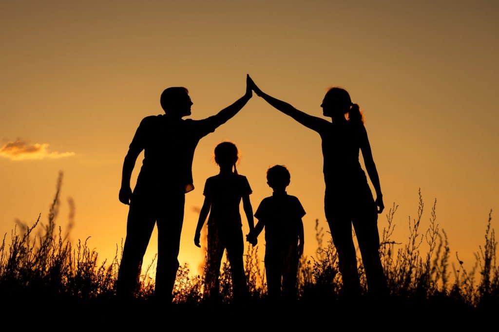 Silhueta de família composta por homem, mulher, menino e menina, todos em um campo com o pôr do sol.