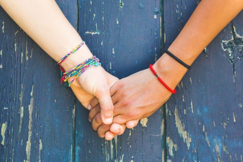 Mãos dadas em frente de um fundo de madeira. Uma mão é de pessoa branca e outra é de pessoa negra.