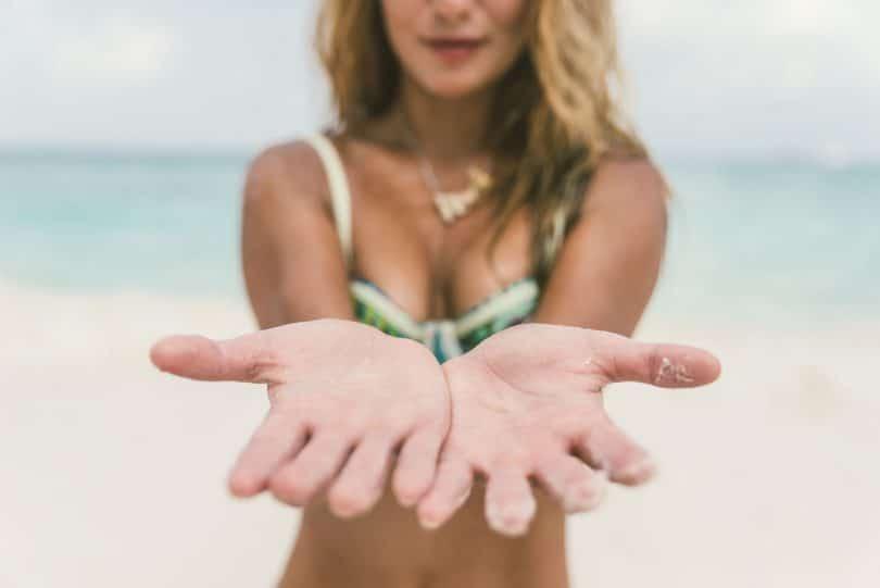 Mulher na praia com as mãos estendidas para a câmera. Ela tem o cabelo loiro e usa um biquíni verde.