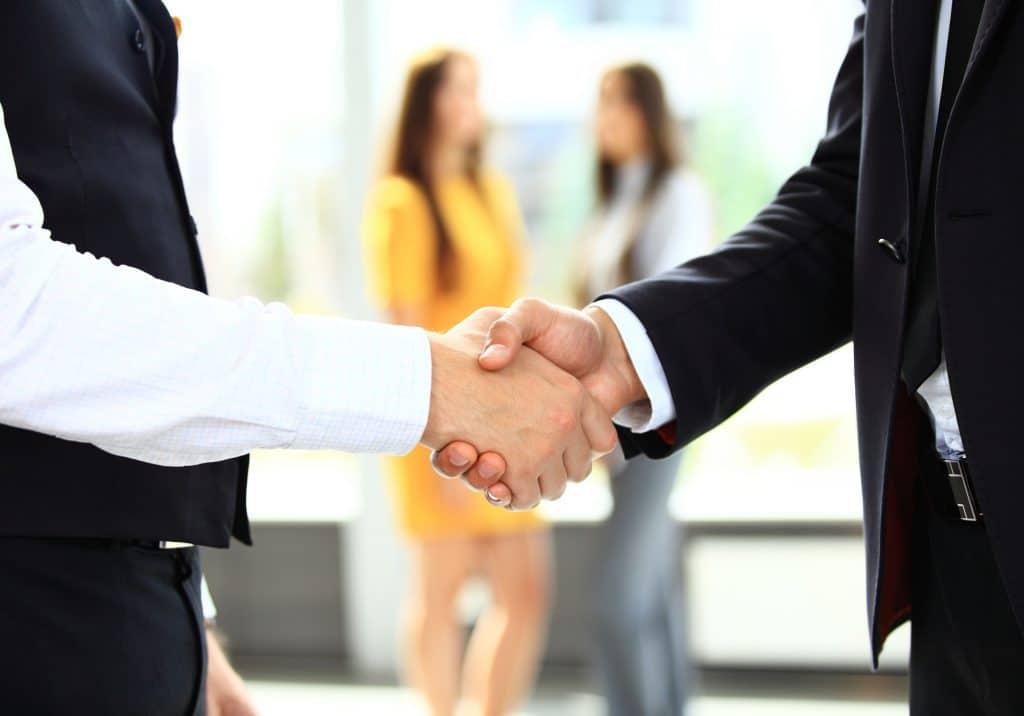 Duas pessoas vestidas de roupas sociais se cumprimentando com um aperto de mãos.