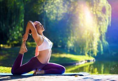 Mulher praticando yoga, vestindo roupas de ginástica, em um parque, próximo à um lago.