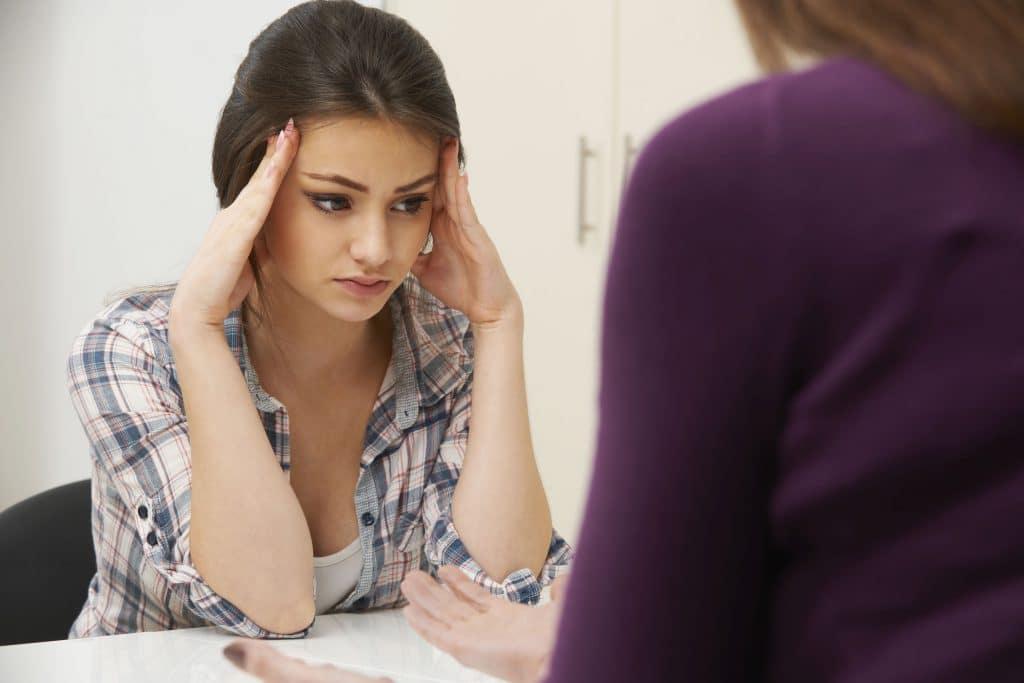 Menina branca, jovem, vestindo uma camisa quadriculada, preocupada apoiando a cabeça nas mãos, em cima da mesa de um consultório médico.