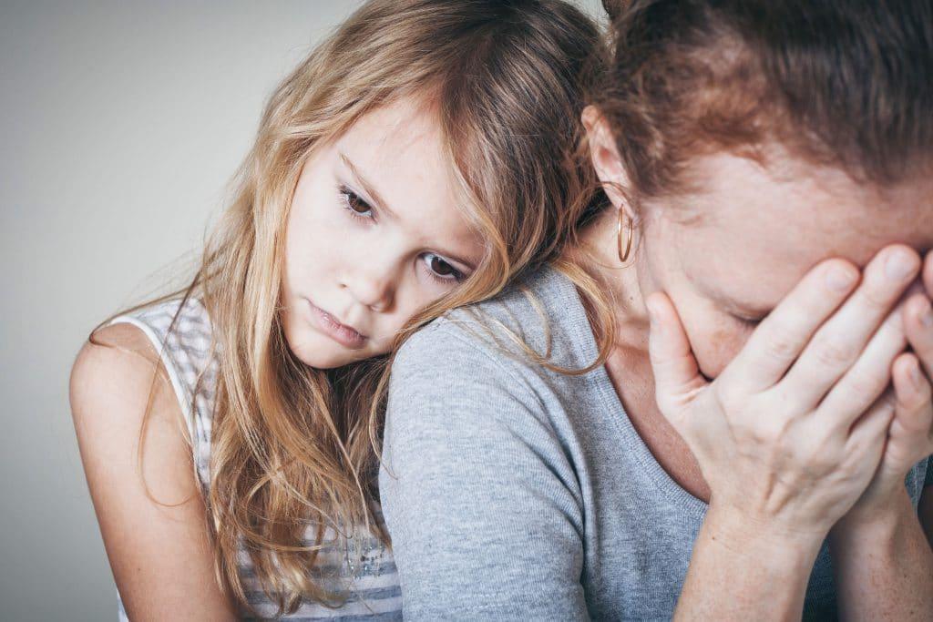 Menina criança branca, com expressão preocupada e triste, apoiando sua cabeça no ombro de sua mãe.