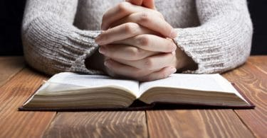 Mãos femininas juntas em sinal de oração, colocadas em cima de uma bíblia posicionada em cima de uma mesa de madeira.