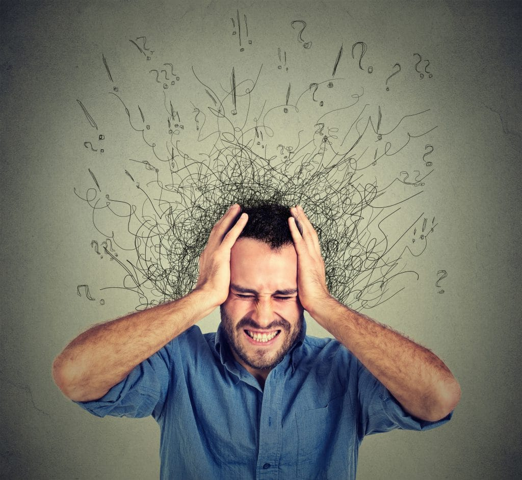 Homem branco, com camisa azul, apertando a cabeça com uma expressão de dor e preocupação, com diversos desenhos confusos ao redor da sua cabeça.