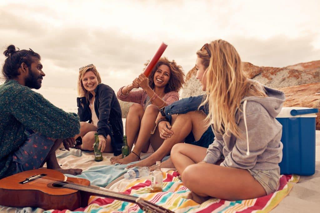 amigos de diversas etnias, todos sentados em cima de uma canga na areia da praia, conversando e rindo.
