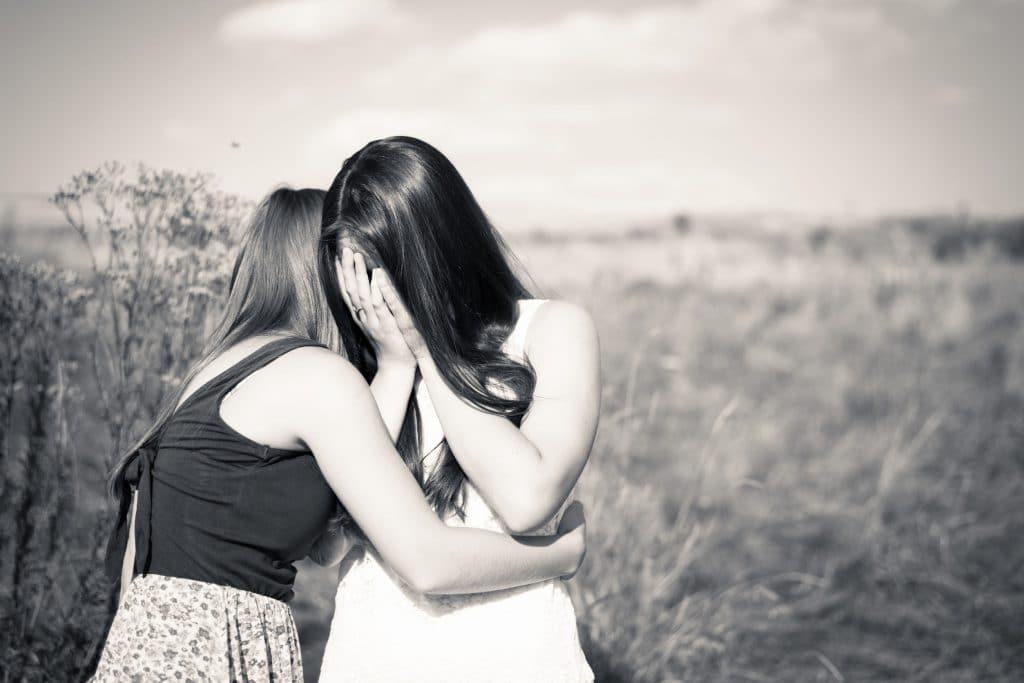 Foto preta e branca de duas adolescentes se abraçando, uma delas esta chorando enquanto a outra tenta conforta-la.