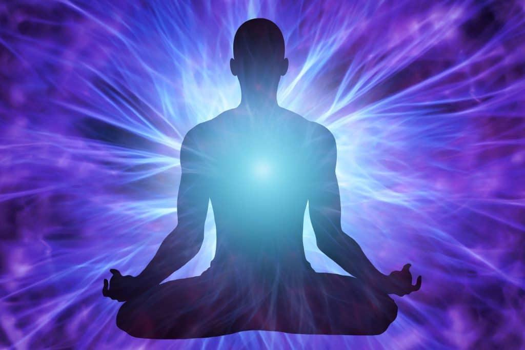 Silhueta de homem meditando com luz no peito.