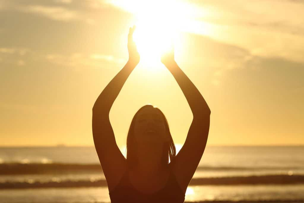 Mulher feliz na praia com os baraços para cima, tentando alcançar uma luz no céu.