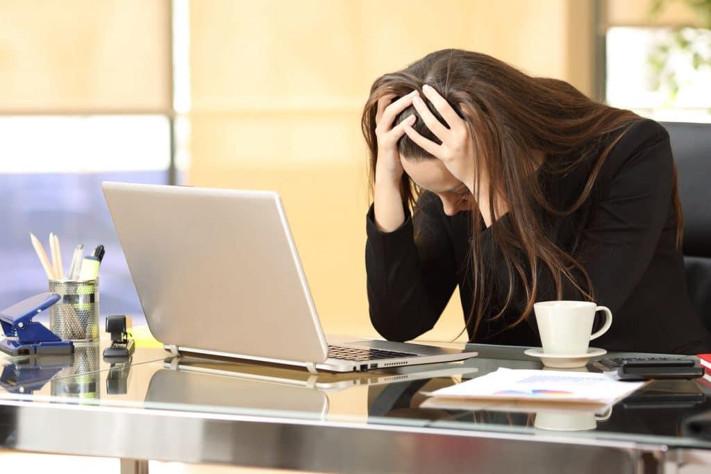 Mulher branca, vestida de social, sentada em uma mesa de escritório, apoiando a cabeça nas mãos, em cima da mesa.